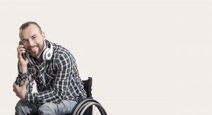 Mann im Rollstuhl mit Handy an dem Ohr.